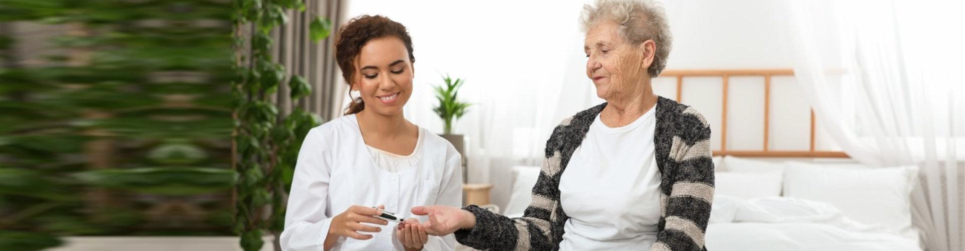 caregiver checking senior woman's blood pressure
