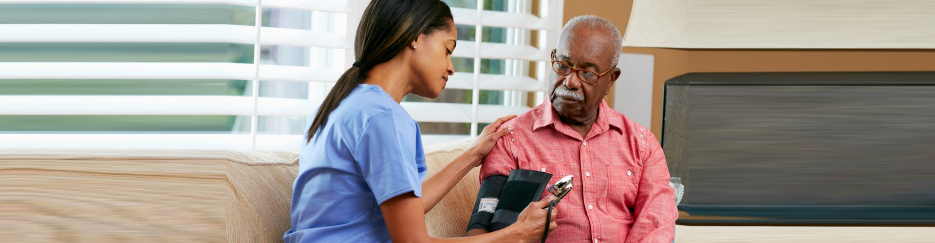 nurse checking senior man's blood pressure